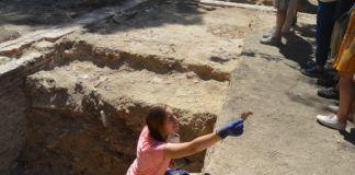 Una arqueóloga entrega un trozo de hueso recién hallado en el yacimiento.
